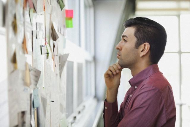 Creativo leyendo notas en un panel de corcho